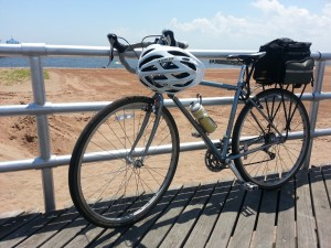 Bicycle leaning against rail on boardwalk; overlooking ocean
