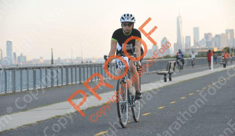Allie on her bike, riding along the Hudson River on Shore Parkway, with 1WTC in the background